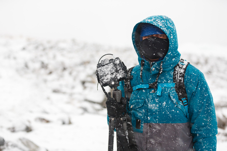 Portrait of a traveling photographer with a camera during a snowstorm