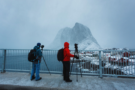 rack mount: Two photographers take a pictures of Hamnoy village during the snowstorm