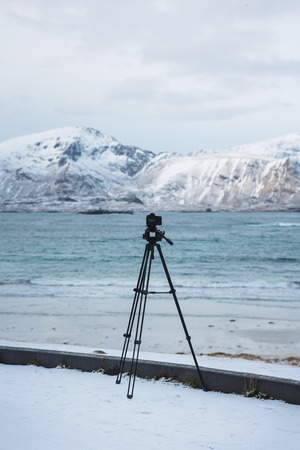 rack mount: Tripod with camera on the snowy shore of Lofoten islands in winter Stock Photo