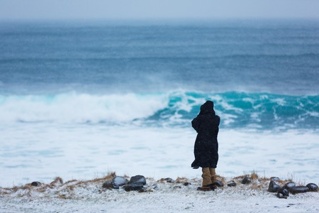 The man is standing on the snowy coast of the north sea