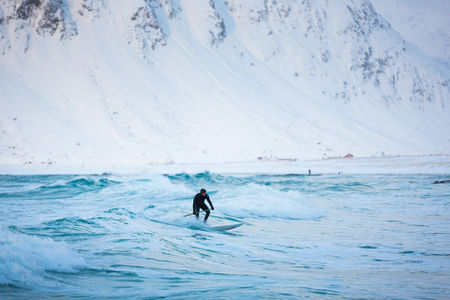 Flakstad, Norway - March 18 2017: Surfer are training on the Skagsanden beach of the Lofoten Islands