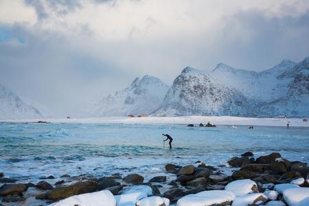 Surfer are training on the Skagsanden beach of the Lofoten Islands Reklamní fotografie