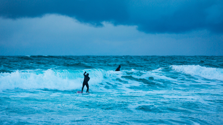 Surfer are training on the Skagsanden beach of the Lofoten Islands Stock Photo