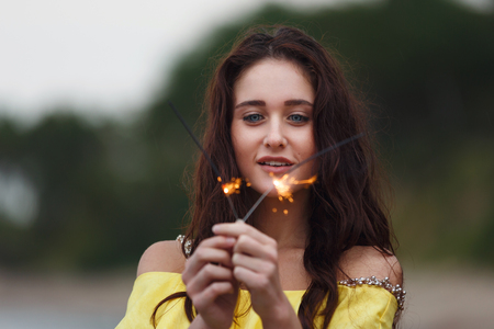 夜のビーチで花火を持つ美しい少女