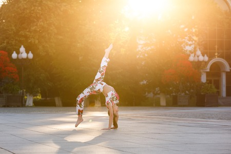 Young gymnast is training on a deserted street in summer Stock Photo