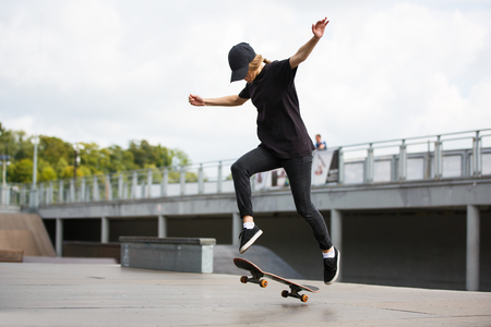 Young female skateboarder practicing in skatepark outdoors