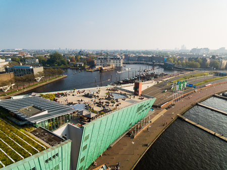 Amsterdam, Netherlands - September 24 2017: Some tourists are resting on the roof of NEMO Science Museum, view from above