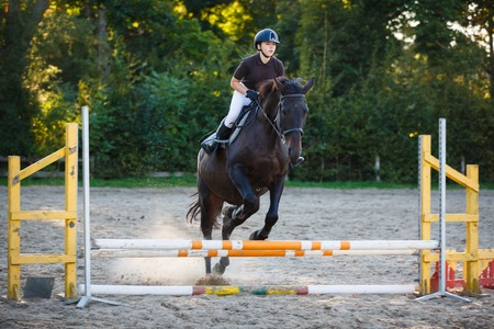 Horsewoman is jumping over obstacle on the competition outdoors