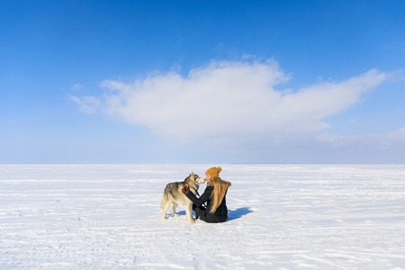 Woman with sled dog on the frozen bay in winter
