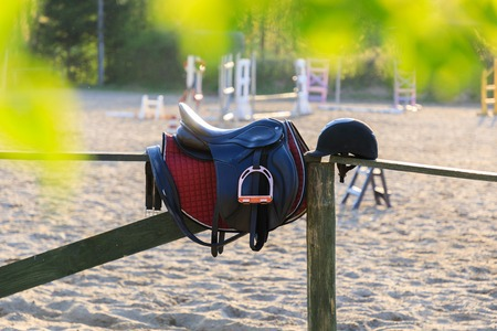 Horseback saddle on the wooden fence in a sunny day Stock Photo
