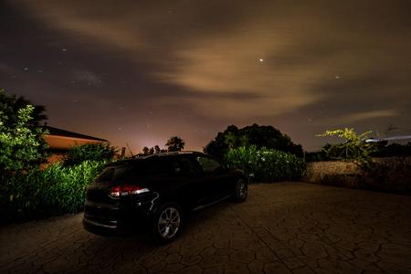 The car under cloudy night sky, long exposure