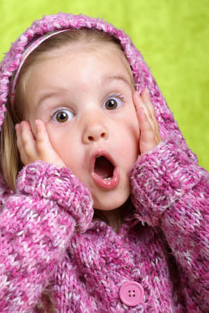 Surprised a beautiful little girl in the pink sweater on green background
