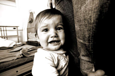 Small frightened baby with his mother in bedroom photo