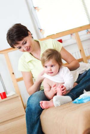 Young mother dresses his little daughter Reklamní fotografie