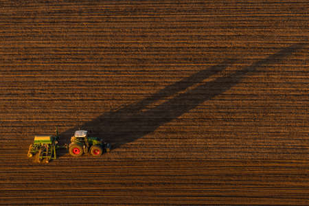 Aerial view of a tractor occupying an autumn field