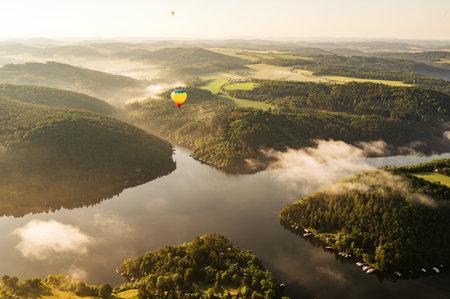 Hot air balloon floating in the morning light over Slapy dam Reklamní fotografie