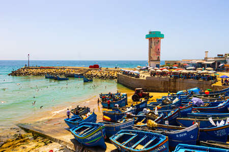 Agadir, Morocco - 14 AUGUST 2020: The harbor of Imesouane. Blue boats, seagulls, a tractor, coffee, fishermen, people swimming, and a control tower Banque d'images