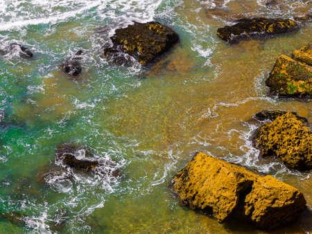 Clean water and brown rocks 写真素材