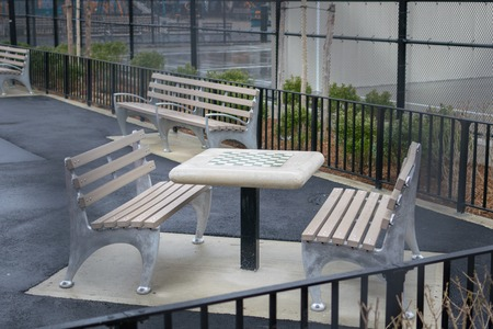 Chess table and empty benches in a park in Williamsburg, Brooklyn, on a rainy day, New York City, USA Stock fotó