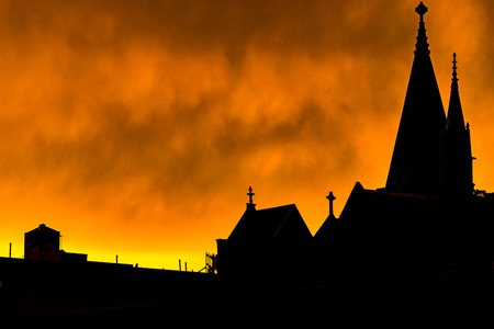 Silhouette of a Harlem rooftop, chimneys, and some church steeples, against a bright yellow fiery-looking sky during sunset, Harlem, New York City, USA Reklamní fotografie