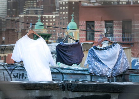 Laundry day in New York City, clothes drying on a Manhattan rooftop, among graffiti and skyscrapers, close-up