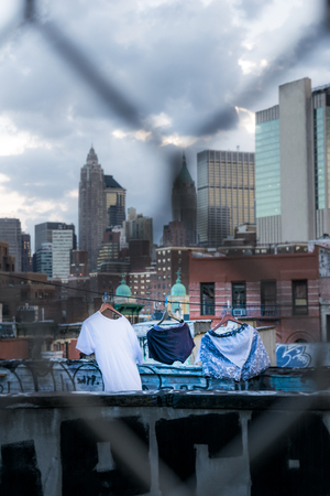 Laundry day in New York City, clothes drying on a Manhattan rooftop, among graffiti and skyscrapers