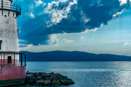 Looking across the Hudson River toward the Jersey Shore with the Sleepy Hollow Lighthouse to the left, with rays of sunlight breaking through the clouds, sleepy Hollow, Upstate New York, NY