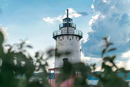 Sleepy Hollow Lighthouse on a beautiful summers day, against a blue sky with white clouds and bokeh foliage in the foreground, medium shot, Sleepy Hollow, Upstate New York, NY