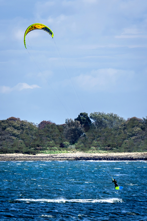 Man taking off during kite boarding on a beautiful sunlit day in Rhodes Island 免版税图像