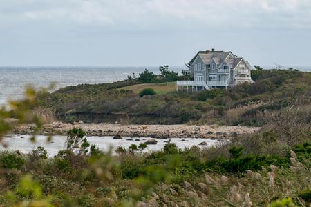 Small house among shrubs and grass overlooking a rocky beach, Block Island, RI