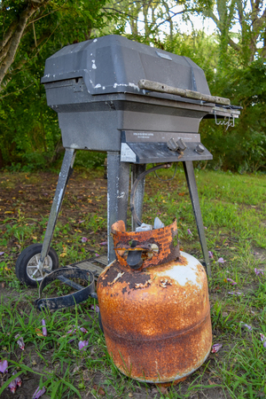 Old and very rusty propane canister and outdoor grill Imagens