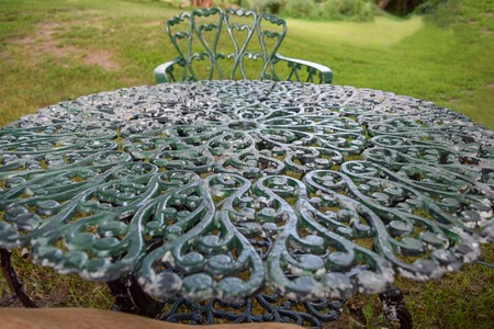 Intricately ornamented cast-iron tabletop in a garden