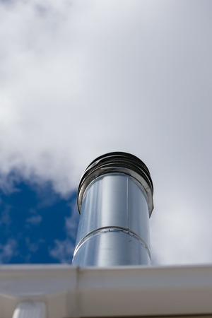 Long chimney pipe reaching into a cloudy blue sky, medium shot, Bronx, NY Standard-Bild - 120964329