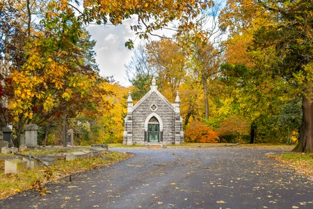 Small mausoleum at Sleepy Hollow Cemetery surrounded by autumnal fall foliage, Upstate New York, NY, USA
