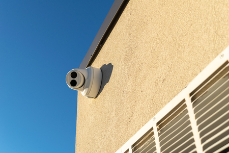 Security camera mounted on a wall, pointed straight at the viewer Stockfoto