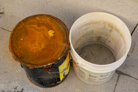 Top-down view of an old rusty metal bucket and a dirty white plastic bucket, close-up