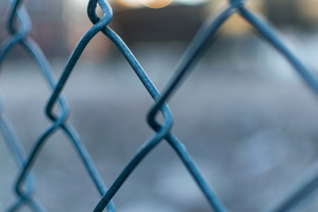 Closeup of a metal mesh fence with blurred out bokeh background