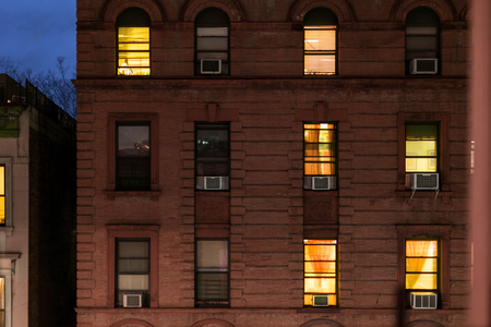 Facade of a typical brownstone apartment building at night, Harlem, New York City, NY, USA