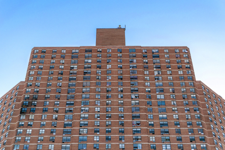 Tall apartment building complex in Harlem, with visible fire damage on the left side, New York City, NY, USA