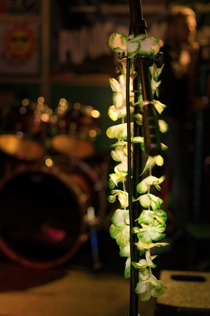 Hawaiian lei hanging from a microphone stand with a blurred out drum set in the background Фото со стока