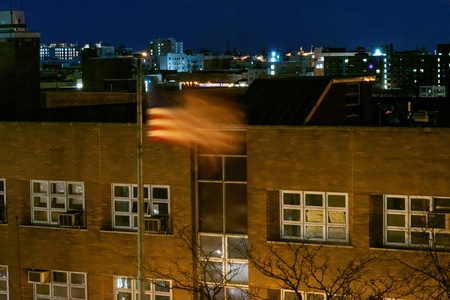 American flag, Stars and Stripes, waving in the wind during a calm and quiet night in the Bronx, NY, USA 写真素材 - 124641931