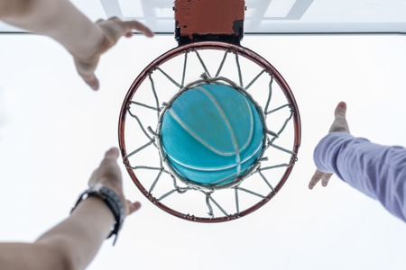 Reaching for a basketball that is in the net Stock Photo