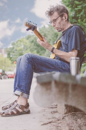 Older male musician playing guitar on a New York City Street