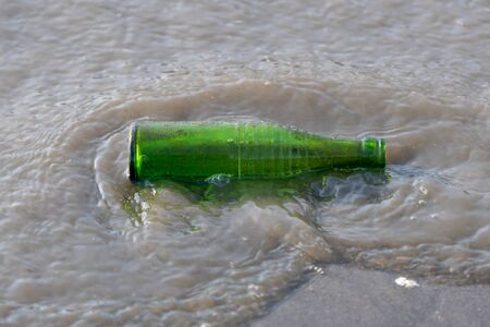 Forlorn green bottle washed up on the shore