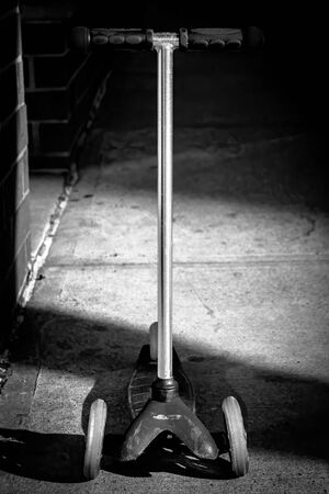 An old and long forgotten scooter standing on the street, black and white