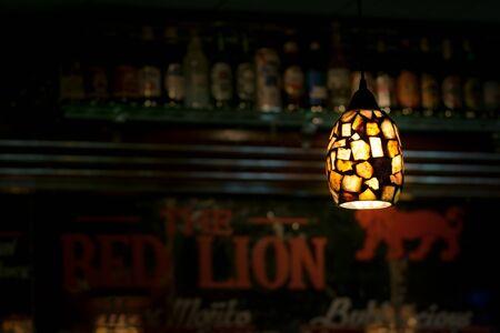 Ceiling light illuminates a dark bar, in New York City 写真素材