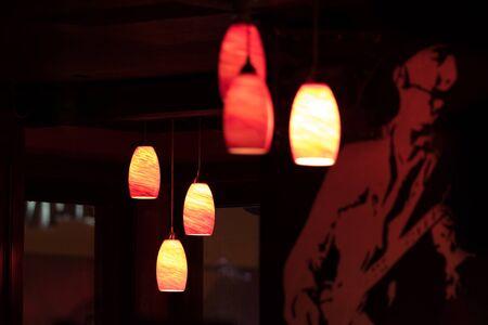 Ceiling lights illuminate a dark bar, in New York City