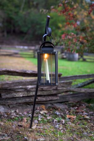 An old-fashioned candle lit lantern during early evening hours