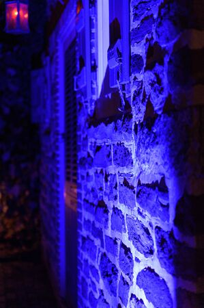 Sideview of an old-fashioned brick and mortar building wall at night, illuminated in blue Stock Photo