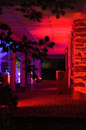 Sideview of an old-fashioned eerie looking brick and mortar buildings porch at night, illuminated in blue Archivio Fotografico